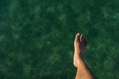 Jump into the ocean. A shot of a person's foot in the air while jumping into the ocean Royalty Free Stock Photography