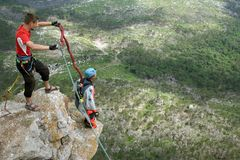 Jump off a cliff with a rope. Stock Image