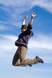 Jump of one happy excited man. Happy man jumping high into the air with blue sky as background Stock Photography