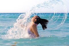 Jump out of the sea. Beautiful woman jumps out of the sea with a big splash Royalty Free Stock Image
