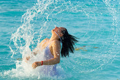 Jump out of the sea. Beautiful woman jump out of the sea with a big splash Royalty Free Stock Image