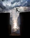 Jump over the abyss. Man Silhouette jumping over the abyss at sunset cloudy sky background royalty free stock photo