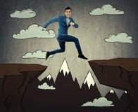 Jump over chasm. Businessman running and jumping over obstacle, across a drawn chasm, with a fearful expression. Symbol of business success, challenge, risk and Royalty Free Stock Images
