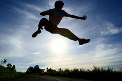 Jump over the sun silhouette Stock Photo