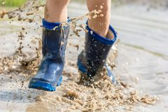 Jump through the puddle as a child stock photos