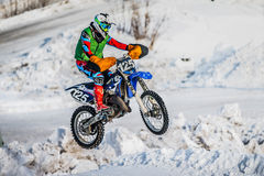 Jump racer on a motorbike over snowy hill Stock Photos