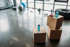 Jump rope and bottles of water on wooden boxes, dumbbells, barbell, training tire, fitness balls, step platform and treadmill. At gym stock image