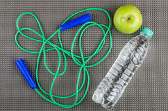 Jump rope, green apple and bottle of water on mat Stock Photo