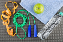 Jump rope, measures tape, green apple on towel and of water Royalty Free Stock Photography