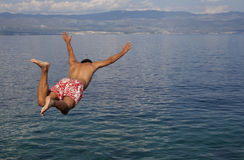 Jump in the sea. Man jumping in the blue sea Stock Image