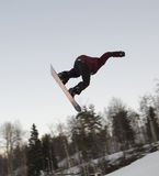 Jump on a snowboard. Man does sports exercises in the snowpark, jump on a snowboard Stock Photography