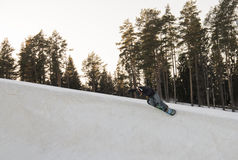 Jump on a snowboard. Man does sports exercises in the snowpark, jump on a snowboard Royalty Free Stock Image