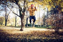 Jump squats in nature. On the move. Stock Photos