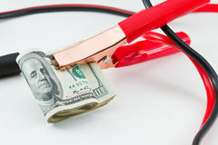 Jump start the american dollar. Booster cables attached to a roll of one hundred dollar bills on a white background Stock Photo