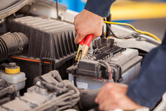 Jump starting a car. Closeup of the hands of a mechanic using jumper cables to start a car Stock Image
