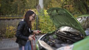 Two not too bright girls trying to recharge a dead car battery. Two girls at the open hood of a car trying to connect to. Jump Starting a car, detail footage of stock video footage
