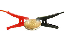 Jump starting the economy with sparks. Photo of two car jump leads connected to a coin with sparks coming from each lead. photo concept depicting jump starting Stock Photo