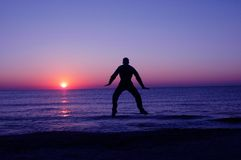 Jump at sunrise. Man silhouette jump in air Stock Image
