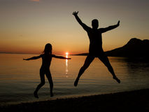 Jump in sunset. Two silhouettes (big and small) of father and daughter  - brother - sister with raised arms jumping into the sunset on the sea. Horizontal color Stock Photos