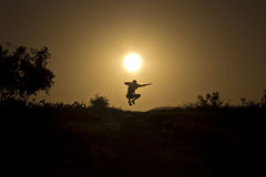Jump at sunset. Man jumping on the background of the stunning sunset Stock Photography