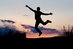 Jump at sunset. Silhouette of man jumping at sunset background Stock Image
