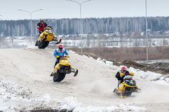 Jump of three sportsmen on snowmobile Stock Photos
