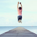 Jump to the freedom. Asian woman jumping on the bridge at the sea Stock Photo