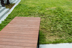 Jump to the grass. Wooden bridge is installed in the garden Royalty Free Stock Photo