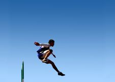 Jump to success!. A hurdler jumps over a hurdle during a track meet Stock Image