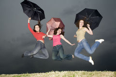 Jump with umbrellas Royalty Free Stock Photo