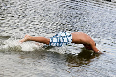 Jump Into The Water. Dynamic Jump Of A Muscular Young Man Into The Water Royalty Free Stock Photos