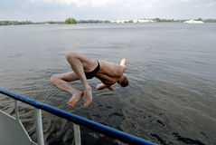Jump in water. Man jump in water from a board of the ship Royalty Free Stock Photography
