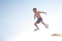 A child boy is jumping into the swmming pool Royalty Free Stock Photography