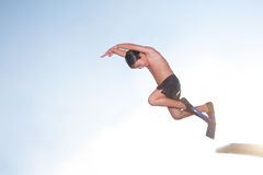 A child boy is jumping into the swmming pool. A child boy is jumping into the swimming pool, with swimfin/swin fins/flippers, flying in the air Royalty Free Stock Photo