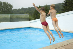 Jump In The Water. Two friends are jumping in a swimming pool royalty free stock photos