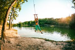 A woman is riding a swing stock image