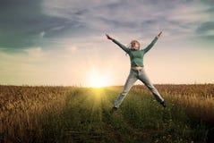 Jump women in wheat field. Portrait of jump young women in jeans in wheat field Stock Photography