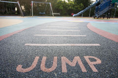 Jump written into rubber floor of playground Royalty Free Stock Photos