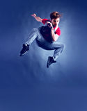Jump. Young street dancer jumps high toned in blue royalty free stock image