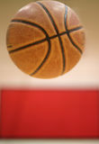 Jumped-up_red. A basketball is jumped-up in the air with blurred red-white wall as background Royalty Free Stock Images