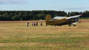 Jumpers board the plane, getting ready for takeoff. Plane sits in a field near the forest in the forest airport small airplane plane for skydiving, extreme stock video footage