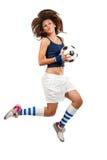 Jumpig de la muchacha con el balón de fútbol Imagen de archivo