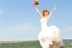 Jumpijng de jeune mariée pour la joie image stock