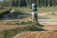 Jumpimg in the air. A motorcross biker jumping in midair Stock Photography