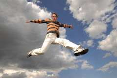 Jumpin'. Young man happily jumping against blue sky Stock Photo