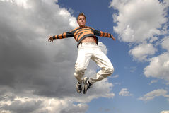Jumpin'. Young man happily jumping against blue sky Stock Photos