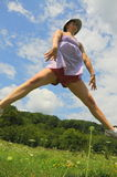 Jumpin Steckfassung (Frau, die einen akrobatischen Sprung tut) Stockfotografie