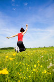 Jumping. A girl wearing sports clothes is jumping a field of spring flowers Stock Images