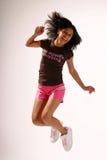 Jumping. Teenage girl with long dark hair jumping royalty free stock image