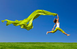 Jumping. Beautiful young woman jumping on  a green meadow with a colored tissue Royalty Free Stock Photo